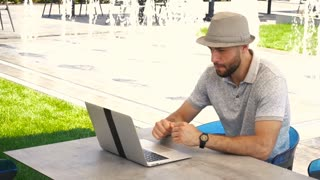 Handsome male fun watching football game with laptop near fountain