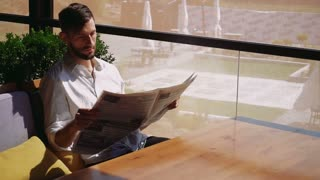 Handsome male person reading newspaper and wondering