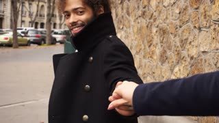 Handsome mulatto boy walking with girl holding hand in slow motion