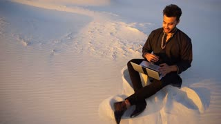 Handsome young Arab man writes on Internet using laptop and sits on sand amid sandy desert at sunset