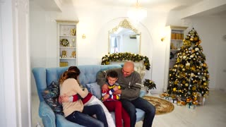 Happy and cheerful family in festive mood have fun and laugh together, sitting on blue sofa in festive decorated room with Christmas tree and fireplace in daytime
