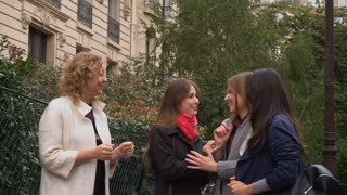 Happy female students talking outside in slow motion near university building