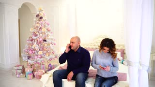 Happy husband and wife use smartphone to congratulate relatives on holidays, sitting on bed in bedroom with festive Christmas tree