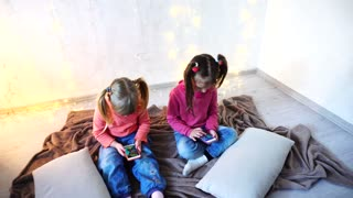 Happy little girls use smartphones for entertainment and sit on floor in bright room with garland on wall