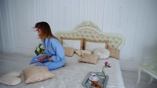 Happy Young Woman Overjoyed, Happy Test Positive For Pregnancy, Smiles and Shows Test Chamber, Sitting on Bed in Bedroom.