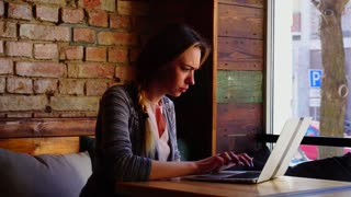 Hardworking copywriter typing article by laptop keyboard at restaurant. Concept of freelancer working at cafe. Young woman sitting near brick wall has pigtail hairstyle.