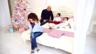 Headache and fatigue of woman, experiences before holidays. woman sits on bed on background of husband and children in bedroom with Christmas tree