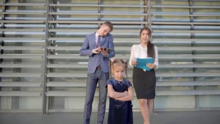 in Foreground Stands Little Girl and Angry, on Background Young Women and Man Talking on Phone and Stand Near Business Center in Neutral Colors.