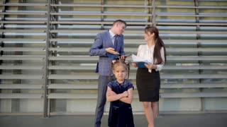 in Foreground Stands Little Girl on Background Women and Handsome Man on Background of Business Center Outdoors in Neutral Colors.