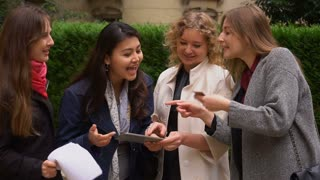 International students paying with card with tablet in slow motion near university building