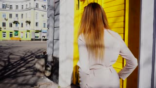 Jocund girl opening yellow door, waving hand and entering cafe. Concept of welcoming female person and having break. Young woman has blonde hair and cute smile.