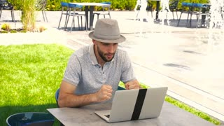 Jocund male person enjoying successful bet on bookmaker site with laptop near fountain