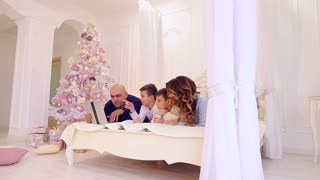 Joint leisure of large and friendly family with gadget on bed in bright bedroom with Christmas tree and decorations