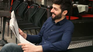 Journalist with close up face reading newspaper article at cafe table in slow motion