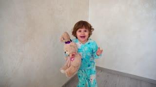 Joyful girl dancing with bunny in arms