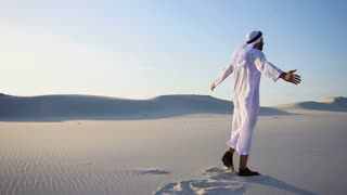 Joyful male Arabian Sheikh Muslim walks through white sand desert and enjoys life on sunny summer day