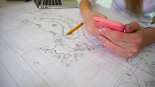 Landscape designer sitting near table with whatman paper and finding new ideas using web