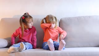 Little girl sitting on couch and crying, friend calms and embraces baby