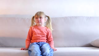 Little girl sitting on couch and crying, mother screaming at child for bad behavior