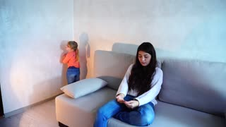 Little girl standing in corner of room, mother punished child for bad behavior