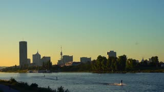 Long river Danube in park flows in Austria s city Vienna. People surf at sun sets uses stretched ropes over river. Men surfing on board at weekend, after work. Conception of places for rest expulsions