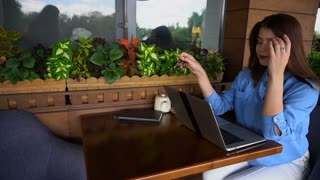 Сlose up face of gladden customer browsing by laptop in slow motion at restaurant