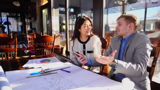 Male architect advising with female graphic designer using project and smartphone at cafe