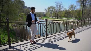 Man reading business papers and dog runs in slow motion on bridge