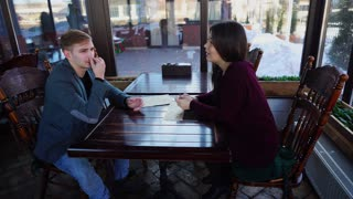 Married couple discussing relocation in coffee house