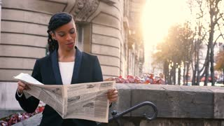 Mix blood woman reading newspaper outdoor with close up of face