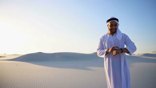 Modern male sheikh uses smart watch and stands in middle of bottomless desert under scorching sun in morning