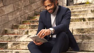 Mulatto businessman using tablet and sitting on steps in slow motion