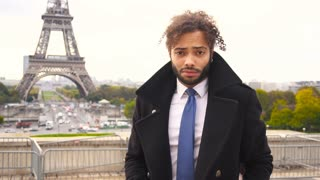 Mulatto male model smiling near Eiffel Tower in slow motion