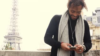 Mulatto male person chatting with friends by smartphone with earphones near Eiffel tower