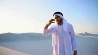 Muslim man feels headache and general malaise, suffers from standing in middle of sandy desert on warm summer day