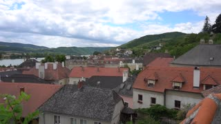 Old houses with red roofs near Danube river and green hills. Village in Austria next to Linz. Concept of tour in small village rich and cheap apartments