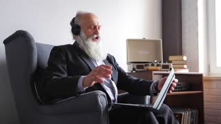 Old Man Enjoys Music and Beats Rhythms, Sitting With Computer in Chair Opposite Window in Daytime.