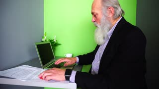 Old Man Head Leader Completes Working Day, Sitting at Laptop at Table in Modern Office.