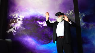 Old Man Plunged Into Google Maps Street View Mode For Virtual Reality and Set Off on Virtual Journey Standing in Front of Bright Wall.