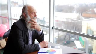Old Man Thinking Aloud About Country's Economy, Sitting at Table in Company's Main Office Near Window.