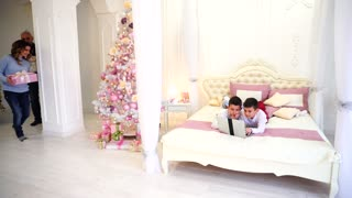 Parents make unexpected surprise for children and spend time together with sons in beautiful bedroom with Christmas tree