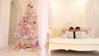 Parents prepared New Year's gifts for their two sons, while boys play games on gadget in newly decorated bedroom with Christmas tree
