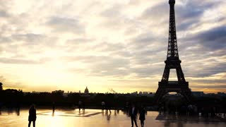 People strolling near Eiffel Tower with sunset background. Concept of walking in Paris near attraction and tourism in Europe.