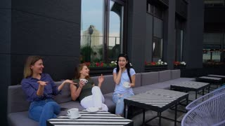 Person in jeans, blue T-shirt very surprised and telling life stories. Girl with ombre sits near brunette woman dressed in khaki T-shirt. Concept of modern cafes for meeting tasty coffee