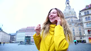 Portrait lovely girls who chat on phone and share impressions about sights of old European city. woman of European appearance with long fair-haired hair stands in middle of old town square Dresden