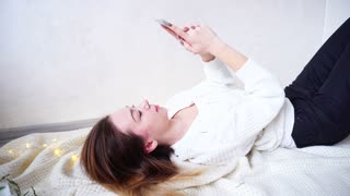 Portrait of attractive Woman in New Year's mood, who writes sms and prints text on touch screen of modern smartphone, lying on back and smiling, looking at phone screen and reading news on Internet