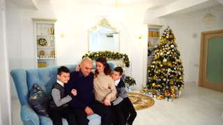 Portrait of charming and exemplary family, caring parents and children who sit on blue sofa in festive decorated room with Christmas tree and fireplace in daytime
