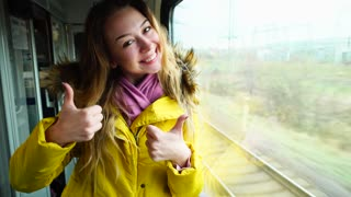 Portrait of cheerful female in train near window. Young woman of European appearance with long blond hair laughing and smiling, showing gestures of thumbs up with hands to camera.  Girl dressed i