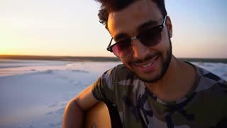 Portrait of close-up portrait of Arab guy who plays guitar strings in endless desert at sunset in open air on summer evening