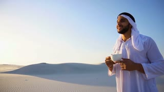 Portrait of handsome young Arabian Sheikh who drinks from cup of coffee, standing in middle of desert against blue sky in open air